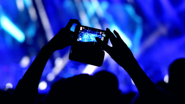 Woman's hand holding a smart phone during a concert video