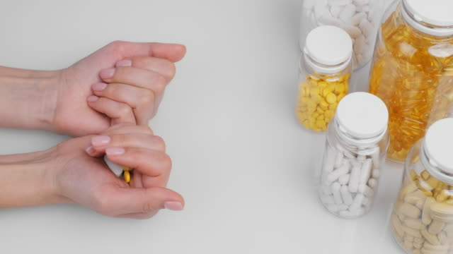 Woman's hand holding orange capsule, white pills in palm hand, left white background bottle tablets. Nutritional supplements, vitamins. Omega 3, multivitamins, Calcium, antibiotics. Health. Close-up