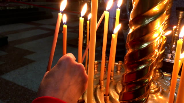 Woman's hand holds and puts a candle in the church. video