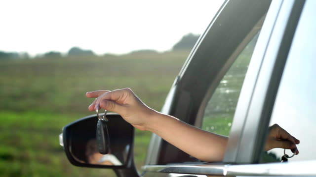 Woman's hand holds out key to the car video