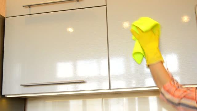 kvinnans hand i en gul gummi handske rengör den blanka ytan av en modern plast kök skåp med en trasa. konceptet med vårstädning och hem arbete - lucia bildbanksvideor och videomaterial från bakom kulisserna