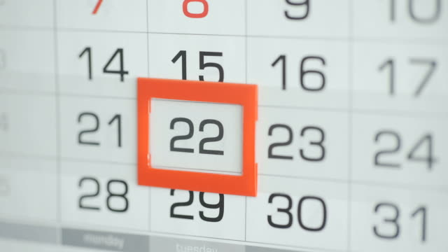 Woman's hand in office changes date at wall calendar. Changes 21 to 22