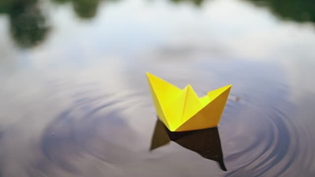 Bидео Woman's hand launches paper boat on the water.