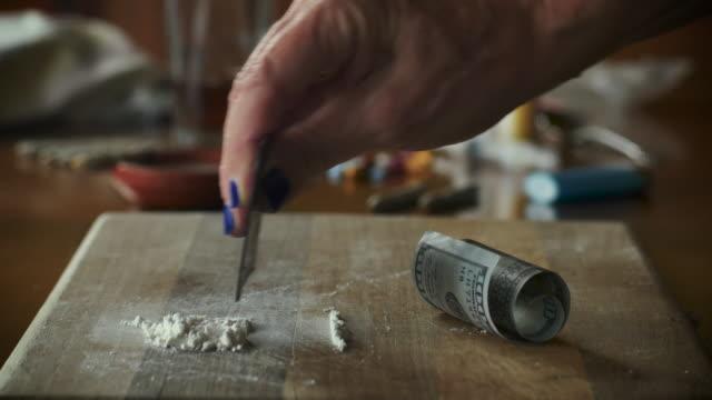kvinnans hand gör linjer med ett vitt pulver som kokain eller meth - amfetamin pills bildbanksvideor och videomaterial från bakom kulisserna