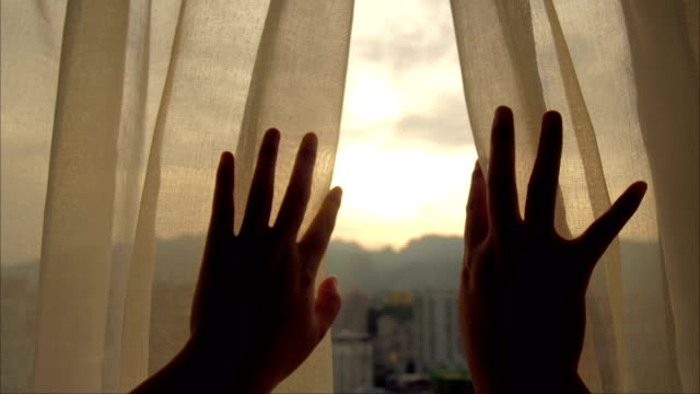 Woman's hand opening curtains in the room