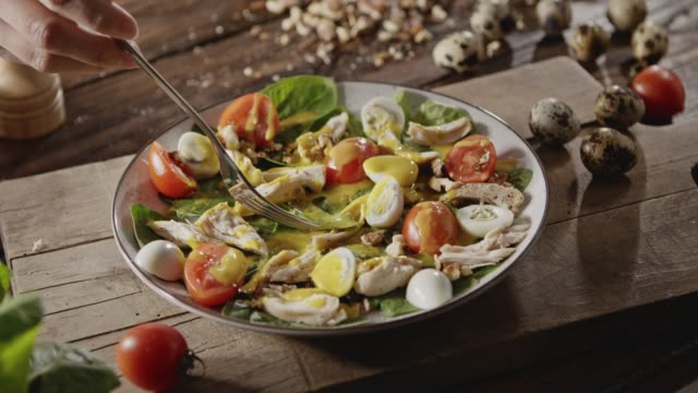 A woman's hand pins with a fork chicken fillet, tomato, shpinach in a plate with salad with quail eggs, chicken fillet, greens, tomatoes, walnuts. Close-up. Slow motion. Full HD video, 240fps,1080p Close-up slow motion video in 4K onto the background with natural organic ingredients for a salad preparation on a wooden board. Delicious healthy organic food with proteins, nutrients and vitamins. fillet stock videos & royalty-free footage
