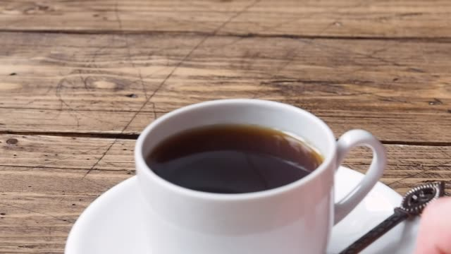 la mano di una donna mette una tazza di caffè nero forte in un piattino sul tavolo di legno. primo tempo - lattaio video stock e b–roll