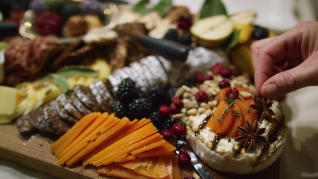 A Woman's Hand Places Star Anise on an Appetizer Charcuterie Meat/Cheeseboard with Various Fruits, Sauces, a Chocolate Log, and Garnishes on a Table at an Indoor Celebration/Party