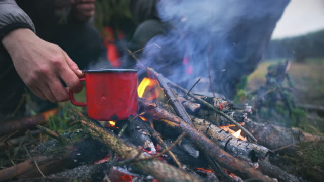 Woman's hand placing a red cup on the twigs in the fire lit in nature