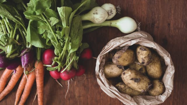 woman's hand placing fresh root vegetables on a wooden table. close up view of raw and homegrown potatoes, spring onions, carrots, radishes and garlic. first harvest in springtime - aglio cipolla isolated video stock e b–roll