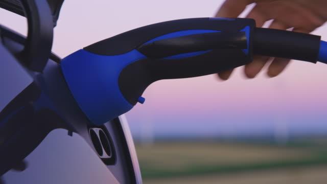 slo mo la mano della donna che collega una spina ev alla sua auto al crepuscolo - collega video stock e b–roll
