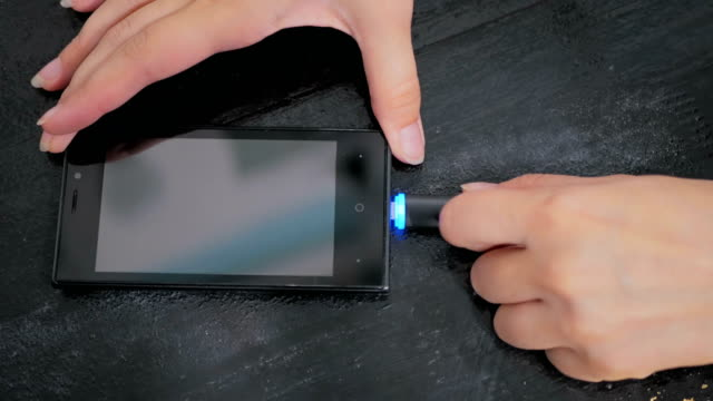 Woman's hand plugging black lightning charging cable into smartphone video