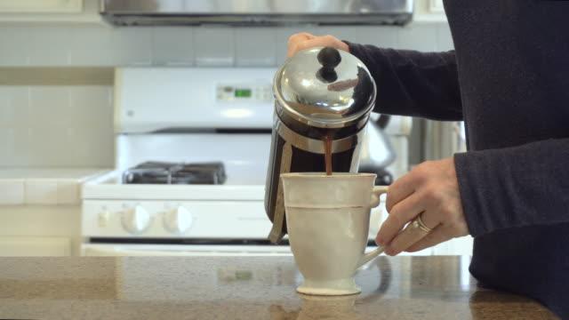 bir fincan kahve dökülen kadın eli - yapmak stok videoları ve detay görüntü çekimi