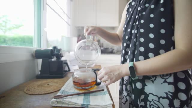 рука женщины наливает чай на кухонный стол дома - погружённый стоковые видео и кадры b-roll