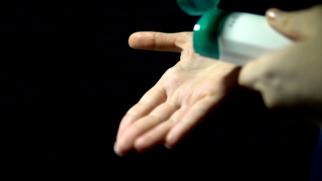 A woman's hand pours a thick cream from a bottle on the palm of your hand video