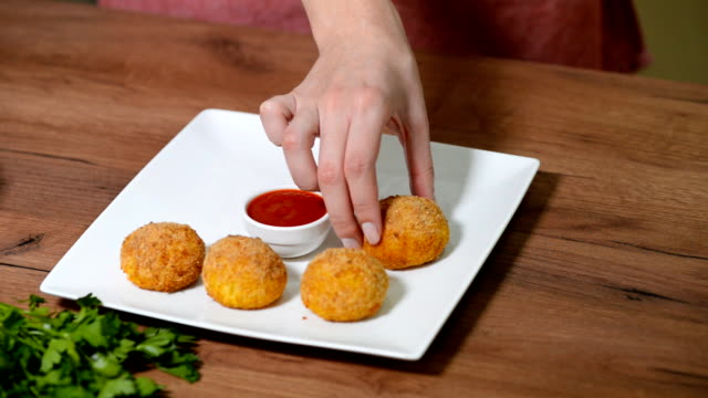 Woman's hand puts a white plate Arancini rice balls Woman's hand puts a white plate Arancini rice balls. stuffed stock videos & royalty-free footage