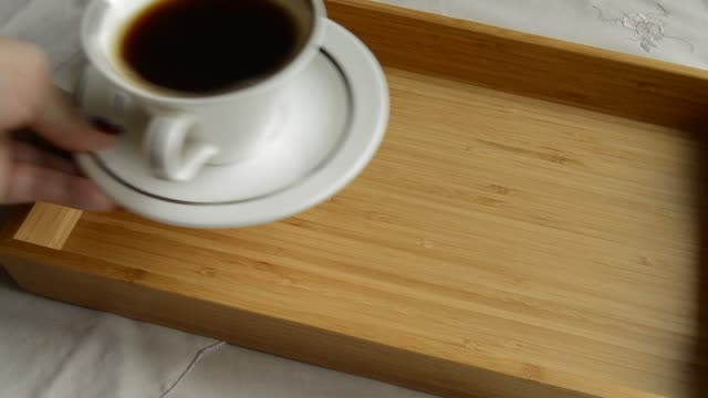 kvinnas hand sätter på trä facket en kopp kaffe och ostkaka på en tallrik - lucia bildbanksvideor och videomaterial från bakom kulisserna