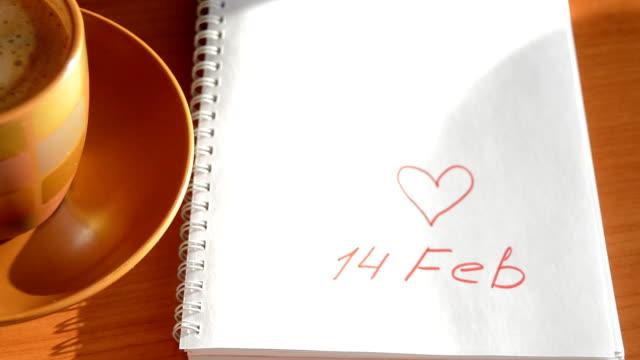 kvinnas hand sätter kaffe koppen nära notebook med tecken hjärtan 14 februari kaffepaus. - lucia bildbanksvideor och videomaterial från bakom kulisserna