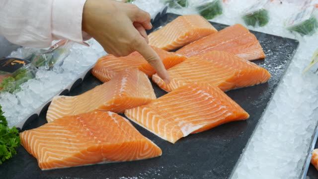 zarte frauenhand einkaufen frische bio-lebensmittel im supermarkt, fisch - fische und meeresfrüchte stock-videos und b-roll-filmmaterial