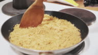 istock Woman's hand stirring bread crumbs with butter in a pan on the stove 1195403390