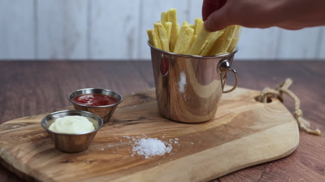 A woman's hand taking a piece of waged homemade fried French Fries and serving it with ketchup from a Mini Serving Basket. Serving chips from a Basket. Concept of serving/eating freshly made chips.