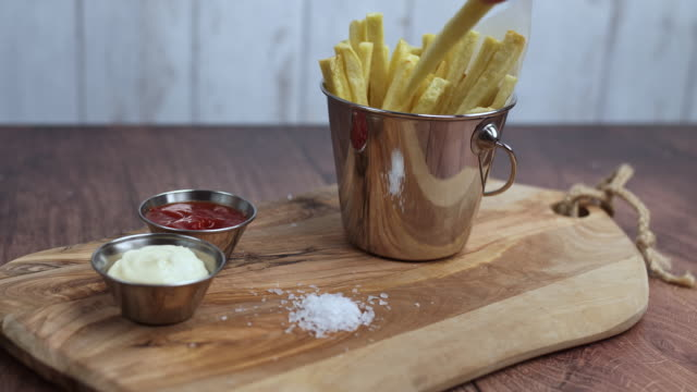 A woman's hand taking a piece of waged homemade fried French Fries and serving it with mayo from a Mini Serving Basket. Serving chips from a Basket. Concept of serving/eating freshly made chips.