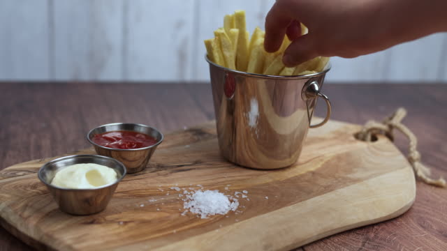 A woman's hand taking a piece of waged homemade fried French Fries and serving it with the sea salt. Serving chips from a Basket. Concept of serving/eating freshly made chips.