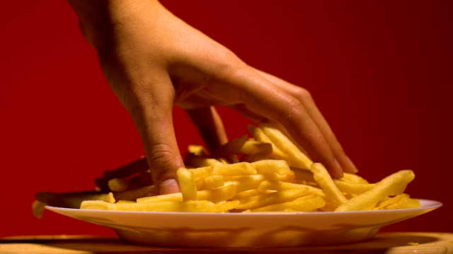 Womans hand taking french fries from plate, junk food addiction, slow motion