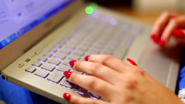 Woman's hand typing laptop video