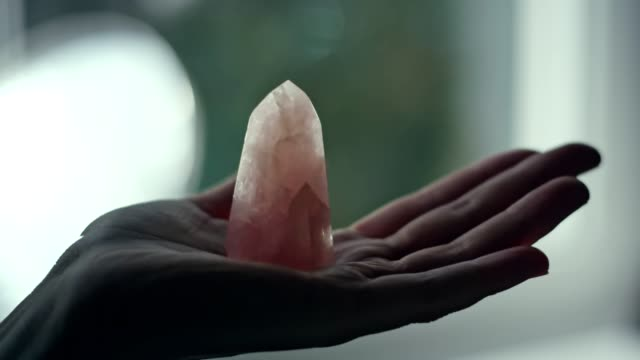 woman's hand with a healing crystal. - кристалл стоковые видео и кадры b-roll