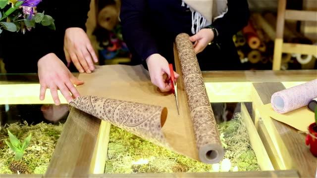 donna di mani con le forbici tagliare la carta di imballaggio fiori. - avvolto video stock e b–roll