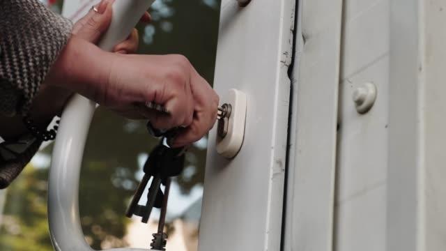 kvinnans händer stänger glasdörren i caféet med en nyckel. låg vinkel. - lås bildbanksvideor och videomaterial från bakom kulisserna