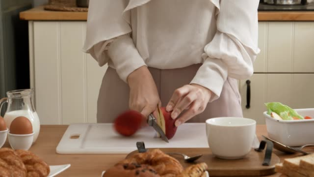 Woman's hands cutting apple