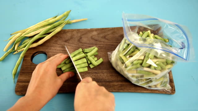 Woman's hands cutting peas and putting in plastic bag to freeze. Frozen vegetables video