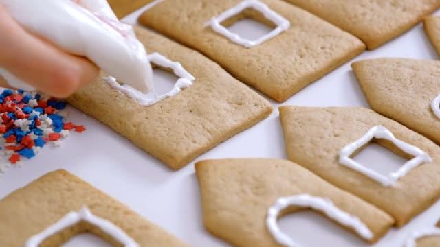 frauenhände schmücken mit zuckersüßen sahnekeksen für lebkuchenhäuser. kochen hausgemachte lebkuchenhaus. - lebkuchenhaus stock-videos und b-roll-filmmaterial