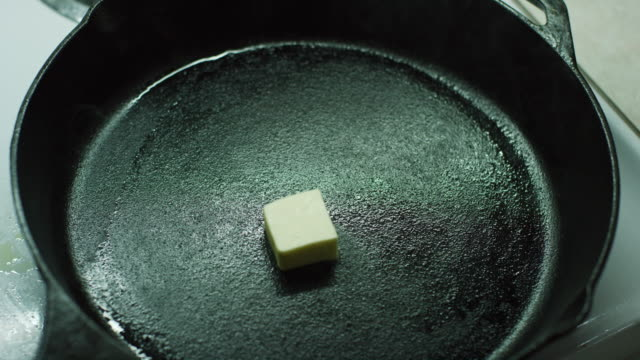 A Woman's Hands Drop Pats of Butter into a Black Cast Iron Skillet on a Stove and then Stir Them with a Wooden Spatula as the Butter Melts A Woman's Hands Drop Pats of Butter into a Black Cast Iron Skillet on a Stove and then Stir Them with a Wooden Spatula cooking pan stock videos & royalty-free footage