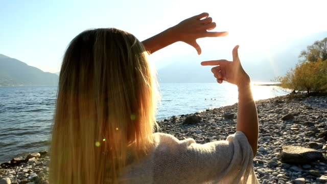 Woman's hands frame sunset over mountain lake video