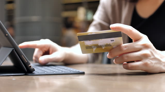 Woman's hands holding a credit card and buying online with a digital tablet, Slow motion video