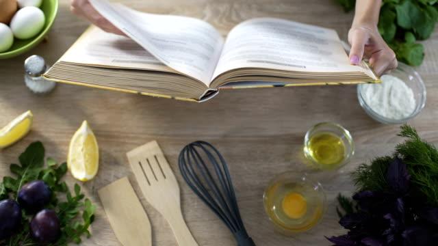 vidéos et rushes de holding de livre de cuisine des mains de femme, fille choisir recette et renversant des pages - recette