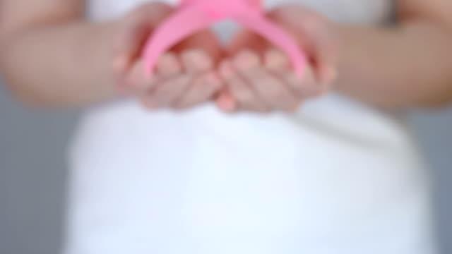 pembe meme kanseri bilinçlendirme şerit - meme kanseri bilinçlendirme kavramı holding womans eller - meme hayvan vücudu bölümleri stok videoları ve detay görüntü çekimi