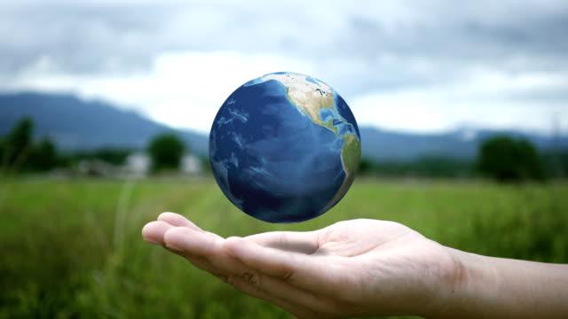 vídeos de stock e filmes b-roll de woman's hands holding spinning globe at outside. - green world