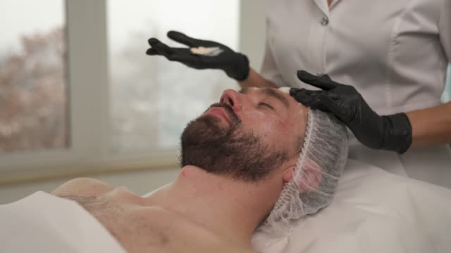 Woman's hands in black gloves applying cream on man's forehead, cheekbones in a beauty salon. The man is lying on the couch and the woman standing at his head Woman's hands in black gloves applying cream on man's forehead, cheekbones in a beauty salon. The man is lying on the couch and the woman standing at his head dermatology stock videos & royalty-free footage