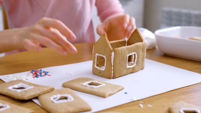 frauenhände machen lebkuchen haus leim details mit zucker süße seise. kochen hausgemachte lebkuchenhaus. - lebkuchenhaus stock-videos und b-roll-filmmaterial