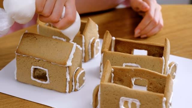 frauenhände machen lebkuchenhäuser leimt details mit zuckersüßem sahnehäubchen. kochen hausgemachte lebkuchenhaus. - lebkuchenhaus stock-videos und b-roll-filmmaterial