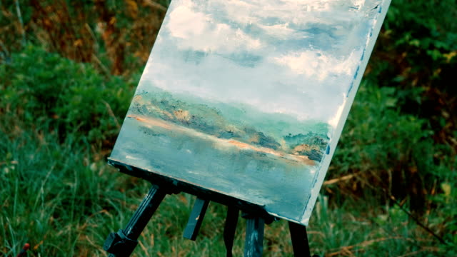 woman's hands painting a water landscape with oil paints using a paintbrush. 4k - cavalletto attrezzatura per arti e mestieri video stock e b–roll