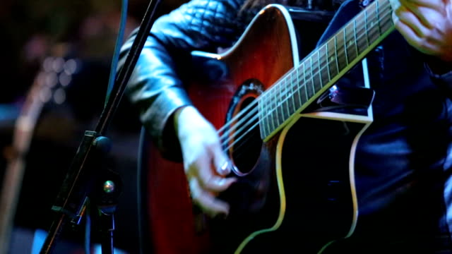 Woman's hands playing acoustic guitar on concert