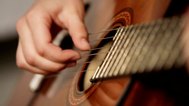 woman's hands playing acoustic guitar Female hand playing on acoustic guitar. Close-up.Female hands on the strings of a guitar. guitar stock videos & royalty-free footage