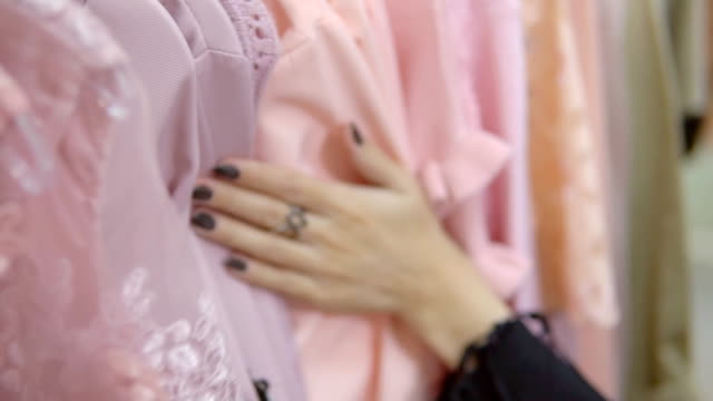 Woman's hands run across a rack of clothes, browsing in a boutique.