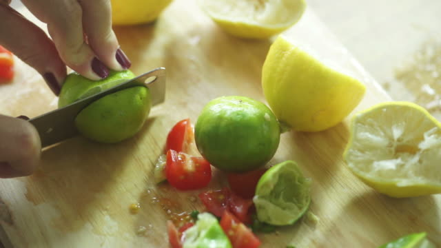 woman's hands slicing lemon on the chopping board - healthy green juice video stock e b–roll