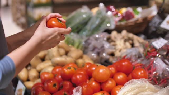 woman's hands take a fruit in supermarket close up - mercato frutta donna video stock e b–roll